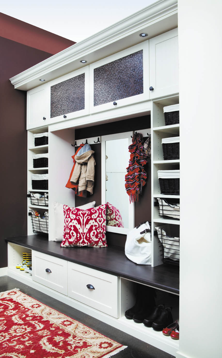 Get organized as soon as you step foot in the door. Shown here: A white entryway mudroom with chocolate and bamboo Ecoresin from California Closets.